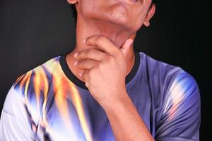 homem segurando a garganta de dor em fundo preto foto