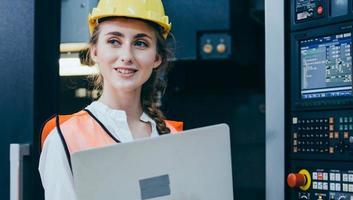 trabalhador da construção civil com um laptop e capacete de segurança foto