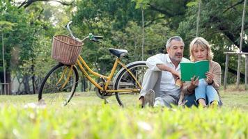 casal maduro lendo um livro em um parque foto
