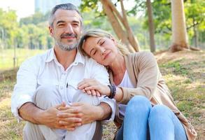 casal sênior caucasiano sentado no gramado do parque