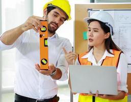 engenheiros discutem projeto enquanto seguram um laptop