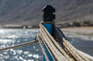 cordas em um poste contra o mar azul foto