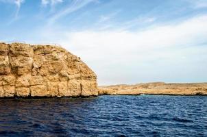 água azul e costa rochosa foto