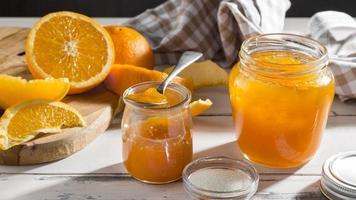 frasco de vidro transparente de alto ângulo com geleia de laranja foto