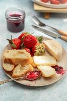 prato de café da manhã com queijo, pão, morangos e geleia, vista de perto