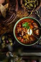 sopa caseira de carne solyanka servida com pão, azeitonas e alcaparras foto