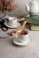 natureza morta com chá escorrendo de uma xícara de chá, livros e flores