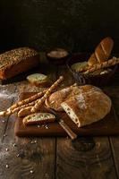 variedade de pães caseiros em fundo escuro e rústico foto