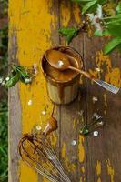 café coreano dalgona em um copo servido em uma velha mesa de jardim amarela em um dia de primavera