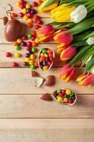 tulipas e ovos de páscoa de chocolate em um fundo de madeira foto