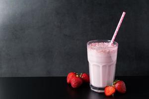 Milkshake fresco com morangos em fundo preto foto