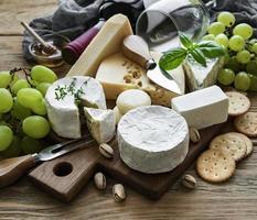 vários tipos de queijos, uvas e vinhos