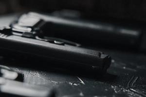três armas em uma mesa preta foto