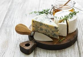 vários tipos de queijo, queijo azul, brie, camembert e mel em uma mesa de madeira