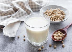leite de soja e soja em uma mesa de madeira foto