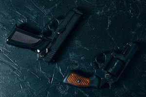 duas armas na mesa preta foto
