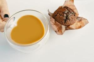 a mão de uma mulher segura a xícara de chocolate e bolinho na mesa branca foto