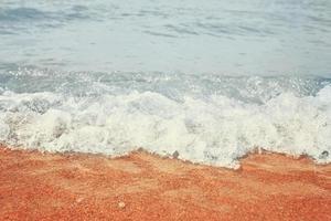 praia de areia com ondas do mar foto