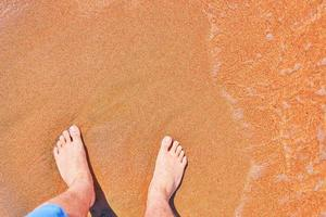 pés do homem na praia foto