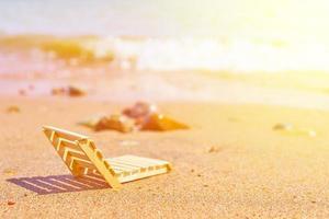 espreguiçadeira de madeira em praia de areia tropical foto
