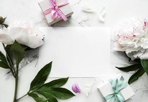 peônias rosa com um cartão vazio e uma caixa de presente em um fundo branco