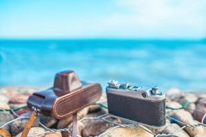 câmera em uma cerca de pedra contra o mar foto