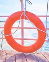 bóia salva-vidas laranja com corda em um píer de madeira perto do mar foto