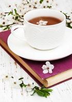 xícara de chá e flores de cerejeira com um livro antigo em um fundo de madeira