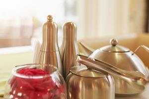 bule de chá de metal com chá, sal, pimenta, açúcar e vaso com flor na mesa foto