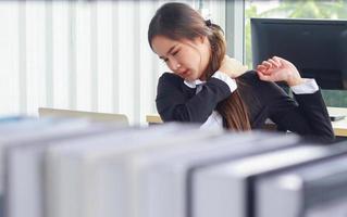mulher asiática no escritório sente dor devido às longas horas sentada