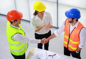 arquiteto engenheiro apertando as mãos no escritório antes de supervisionar o canteiro de obras foto
