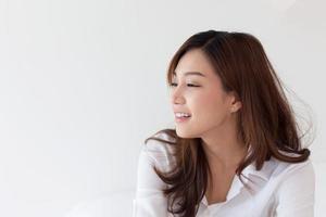 linda mulher asiática sorrindo na cama nas férias foto