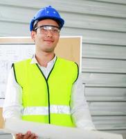 jovem engenheiro em pé com um laptop em uma construção