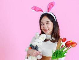 retrato de uma linda garota com um ovo de páscoa em um fundo rosa