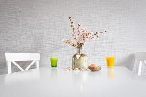 Mesa de cozinha branca em estilo buquê montada com xícaras amarelas e verdes, flores desabrochando e um ovo de páscoa