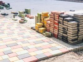 pilha de novos tijolos quadrados coloridos em processo de assentamento para a via de pedestres