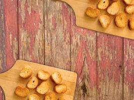 torradas fatiadas em uma tábua de madeira sobre um fundo de mesa de madeira foto