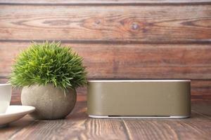 alto-falante e planta na mesa de madeira foto