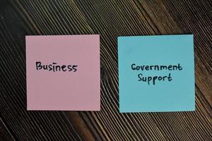 apoio empresarial e governamental escrito em notas auto-adesivas isoladas na mesa de madeira