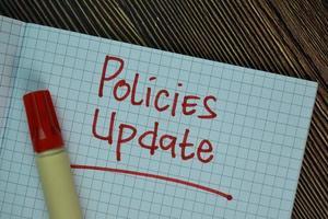 atualização de políticas escrita em post-its isolados na mesa de madeira