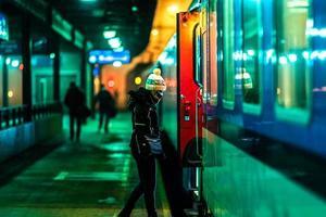mulher embarcando em um trem noturno na estação foto