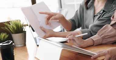 empresária segurando canetas e realizando reunião de jornal para planejar vendas