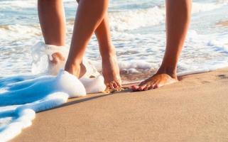 pés descalços caminhando na praia foto