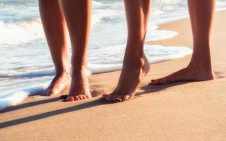 close-up de pés de duas pessoas na areia foto