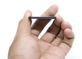mão segurando um cartão de memória compact flash em fundo branco