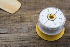Panificação e utensílios de cozinha com cronômetro de cozinha em uma mesa de madeira