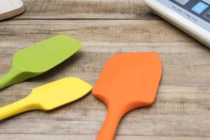 Padaria de silicone e utensílios de cozinha em uma mesa de madeira