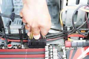 a mão do homem segurando um plugue de alimentação e um cabo para conectar a um computador da placa-mãe