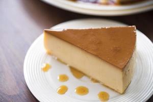 pudim de creme de caramelo caseiro em um prato branco sobre uma mesa de madeira foto