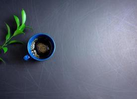 café preto com espuma dourada e folha verde plana sobre fundo riscado foto